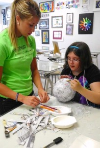 Katie Scherder, a William Woods education student, helps Emma Fennel with her project during last summer's Kemper Kids Summer Creativity Camp at William Woods University.