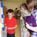Aden Koelling, 10, tells Dr. Mary Spratt, professor emeritus of biology at WWU, and  Jodie Dolan, a pre-vet major from Westphalia, Mo., about his magnets project.