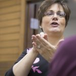 Dr. Barbara Garrett uses American Sign Language to communicate with a Deaf person.