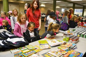 """Children attending the """"Kids Hoo Care"""" day camp help fill backpacks with food and school supplies for Lakota Sioux children at Red Cloud Indian School on the Pine Ridge Reservation in South Dakota."""