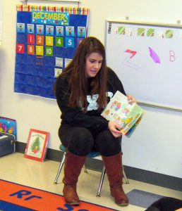 Katharine Carney, who plans to be a teacher, reads a Berenstain Bears book to the youngsters in Fulton Preschool.