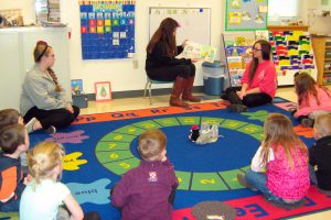 Katharine Carney reads a book to the Fulton Preschool children while Shelby Cobb (left) and Olivia Rush look on.