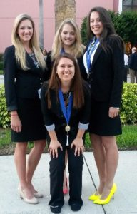 Rochelle Garcia (front) and Taylor Finkel, Tori Brandt and Kara Eikenbary show off the medals they earned at the Collegiate DECA International Competition.