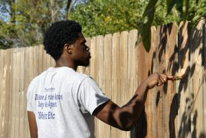 TaiRhe Turner uses a brush to apply stain.