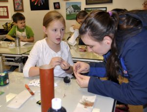 WWU student Heather Cartwright helps Emerson Fansler with her project.