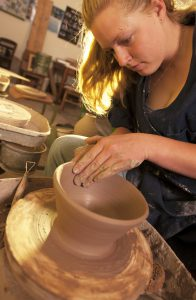 A student tries her hand at the pottery wheel.