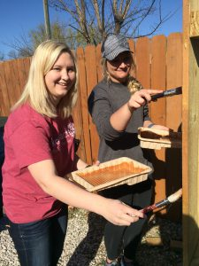 Baylie Borman and Mallory York stain the fence at the Coaltion Against Rape and Domestic Violence (CARDV).