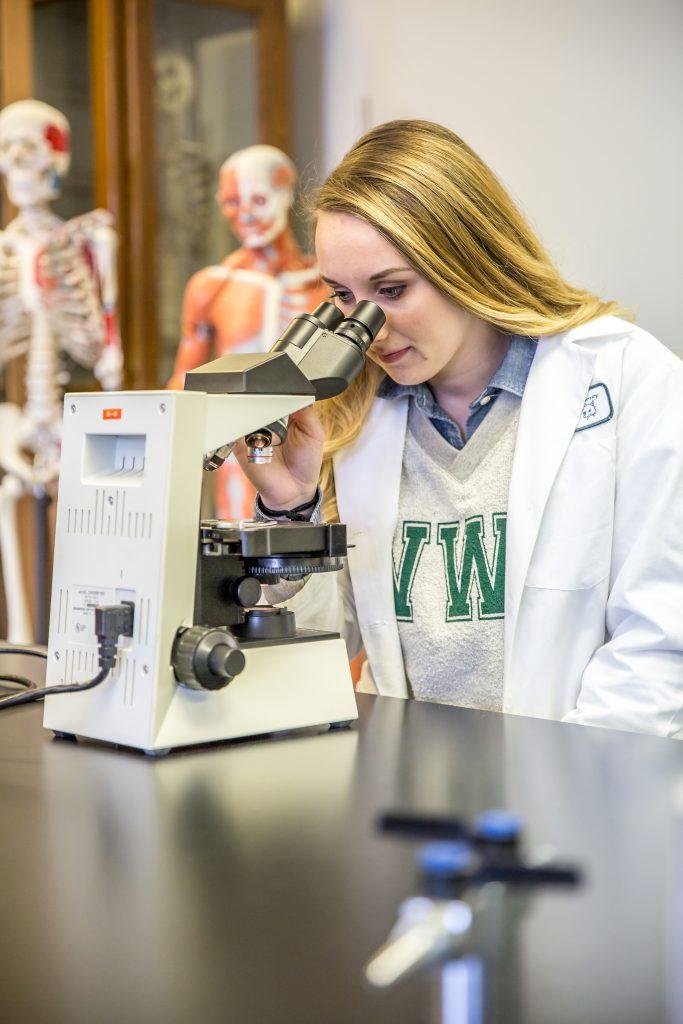 Ari Arnold looking into a microscope
