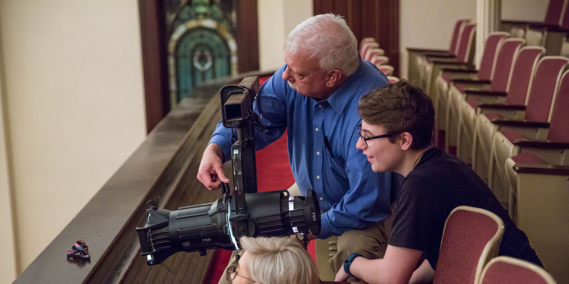 Joe Potter handling lighting equipment with students