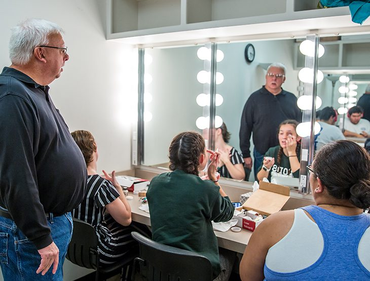 Students working on stage makeup with Professor Joe Potter